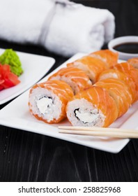 Different Sushi rolls,wasabi and ginger on a plate on wooden background