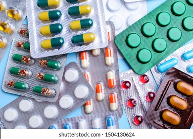 Different tablets, pills in foil blister packs, medications drugs on blue background