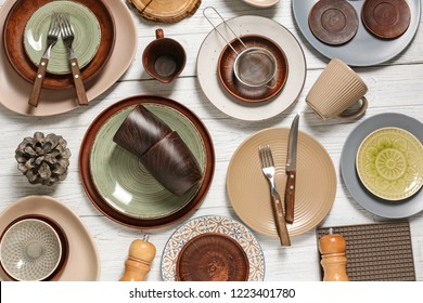 Different tableware and cutlery on wooden table