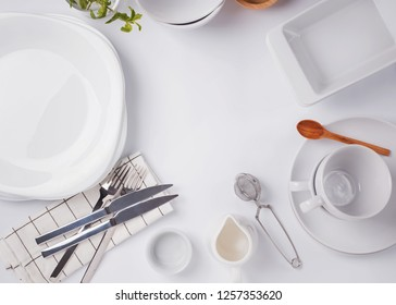 Different tableware and dishes on the white background, top view. Kitchen accessories flat lay.