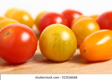Different tomato cultivars on wooden cutting board. Macro. White background.