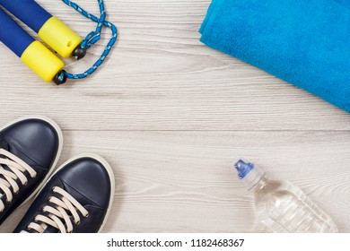 Different tools for fitness with bottle of water in room or gym on grey floor