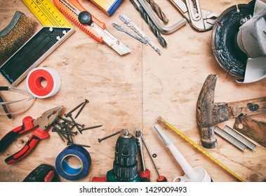 A lot of different tools on the wooden dirty table