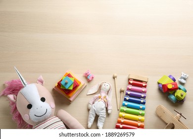 Different toys on wooden background, flat lay. Space for text