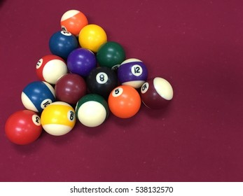 Different type of colour and stripe of pool balls on maroon background