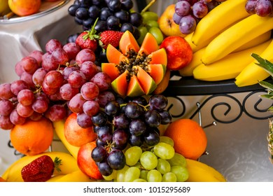 Different type of grapes, papaya and bananas on a table