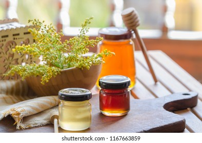 Different type of honey in jar on wooden table in countryside. Honey varieties background