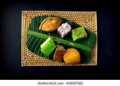 Different type of Malaysian traditional cake, kuih pulut udang, seri muka, kek pisang, karipap, keladi, bingka. served on banana leaf wooden background