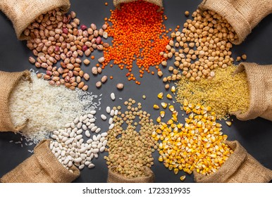 Different type of raw dry legumes composition. White beans, lentils, bulgur, chickpeas, kidney beans, corns, rice, in burlap sack Mix organic legume concept