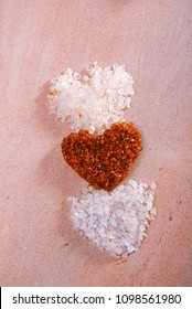 different type of salt in heart shapes , Himalayan Pink Crystal Rock salt,Hawaiian Red Gold Salt,Persian Blue Iranian, on rose marble plate