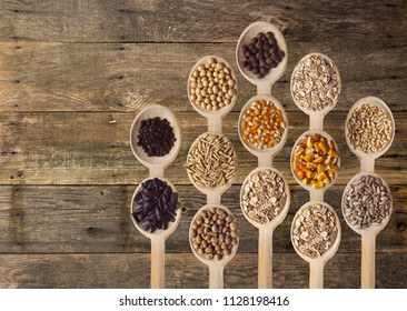 Different type of seeds on wooden spoon. Wooden background