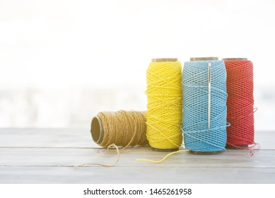 Different type of spool yarn with needle on wooden desk
