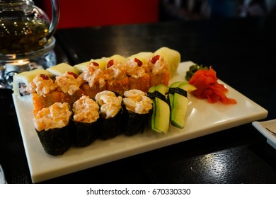 Different type of sushi are puted on a big white square plate. It is all on a black table. In left corner is circle candle. Everything is in deep dark colors under a warm light.