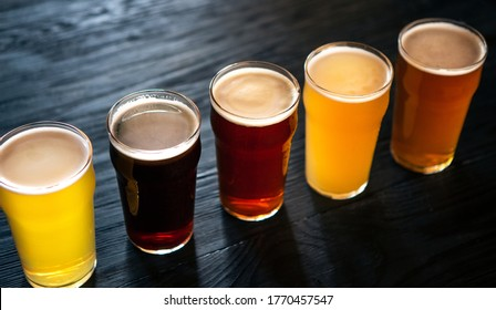 Different types of beers. Ale, dark, light and unfiltered beer and lager, in glasses on dark wooden counter, top view, close up - Shutterstock ID 1770457547