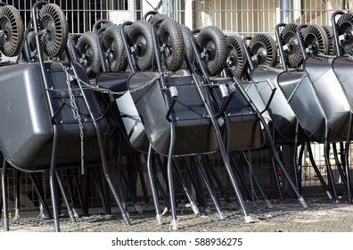 different types of black wheelbarrows ready to sell, tied with string