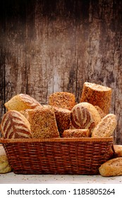 Different types of bread and buns in a metal basket on a wooden background and empty space for text