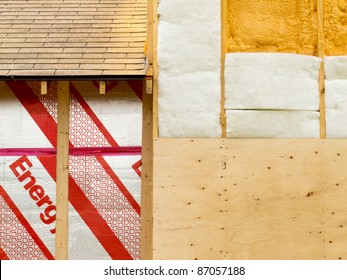 Different types of building insulation: rigid extruded foam sheets, polyurethane spray foam and fiberglass mats.