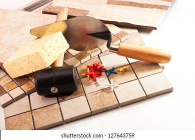 Different types of ceramic tiles, trowel, a rubber mallet, the crosses on a white background