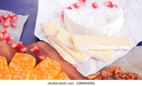Different types of cheese and fruit. Sliced camembert and pomegranate. Soft and hard cheese and nuts. Camembert and grapes on blue background. Vegetarian food