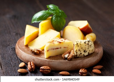 Different types of cheese on dark wooden background