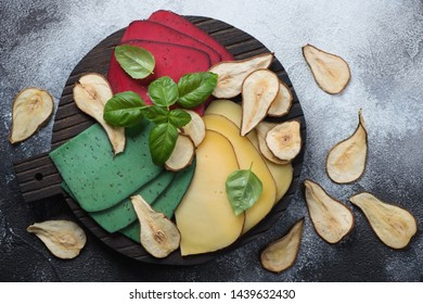Different types of cheese with pear chips and fresh basil, flatlay over grey stone background, horizontal shot