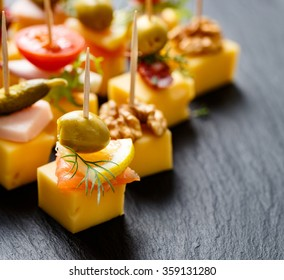 Different types of cheese skewers on a dark background. Delicious appetizers with cheese and various ingredients
