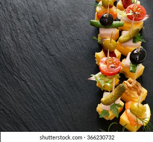 Different types of cheese skewers on a dark background. Delicious appetizers with cheese and mix ingredients