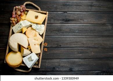 Different types of cheese in a wooden tray with grapes . On a wooden background.