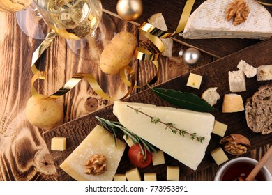 Different types of cheeses on board with walnut and grapes