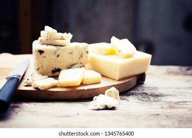Different types of cheeses on wooden board