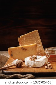 Different types of cheeses. slices of cheese brie or camembert with parmesan, cheddar, with nut and honey on wooden board on dark background