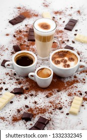 Different types of coffe ,espreso,long coffe ,latte,coffe with milk,on sweet background with coffe beans and chocolate.