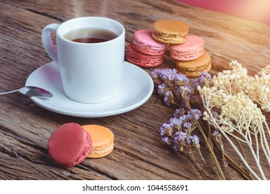 Different types color of macaroons Cup of hot tea on Old grunge wooden background Decorated with dried flowers Vintage style
