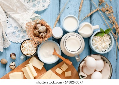 Different types of dairy products on blue wooden background: milk, sour cream, cottage cheese, cheese, cream, yogurt, eggs and butter. Top view with copy space