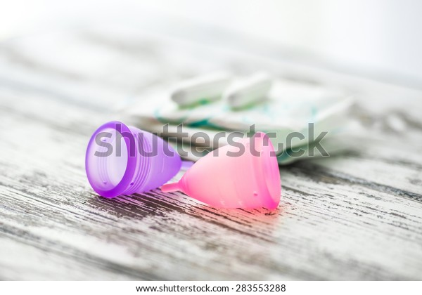 Different types of feminine hygiene products - menstrual cups, sanitary pads and tampons. Selective focus and shallow DOF