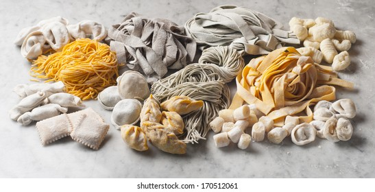different types and flavors of fresh pasta on marble table