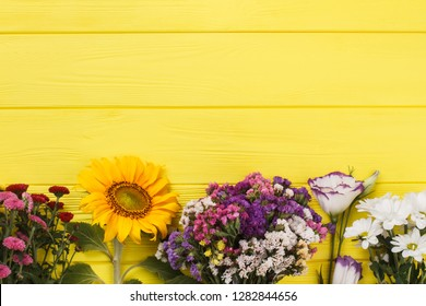Different types of flowers in a row. Yellow wooden table. Dahlia, sunflower, dried limonium statice, lisianthus and chamomile flowers.