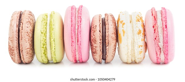Different types of french sweet cookies, macaroons in row. Isolated on white background. Side view.