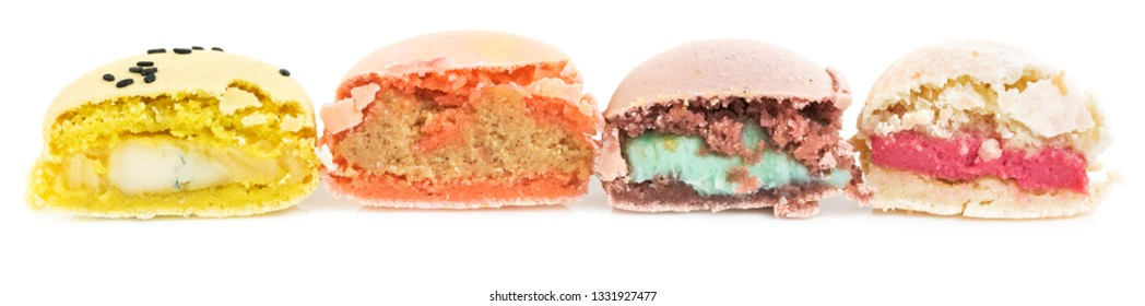 Different types of french sweet cookies, macaroons in row cut in half. Isolated on white background. Side view.