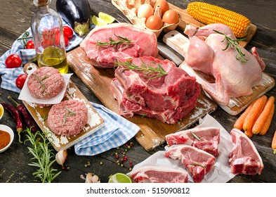 Different types of fresh raw meat with vegetables and herbs on wooden background. View from above