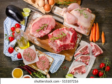 Different types of fresh raw meat with vegetables and herbs on wooden table. View from above