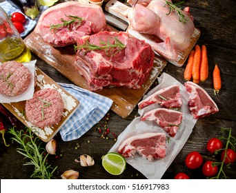 Different types of fresh raw meat with herbs on wooden table.  Top view