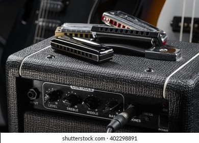 Different types of harmonica are scattered randomly on the top of guitar amp. Ideal musical instrument for playing western and country music.