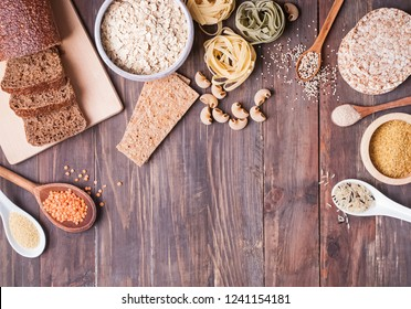 Different types of high carbohydrate food. Flour, bread, dry pasta and lentils and other ingredients on the wooden table.