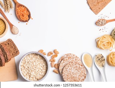 Different types of high carbohydrate food. Flour, bread, dry pasta and lentils and other ingredients on the white background.