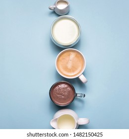 Different types of hot drinks - coffee, matcha, cocoa and white creamers with milk and cream on a pastel blue background. Top view