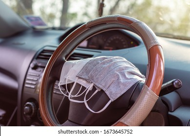 Different types of hygienic masks, both white and gray, are placed in the steering wheel of the car, with the countryside blurred in the background.