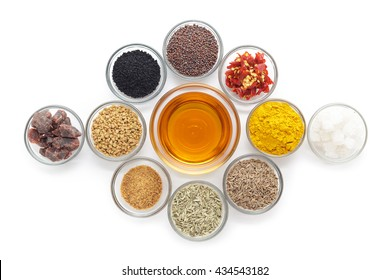 Different types of Indian spices with mustard oil in glass bowl isolated on white background. Top view.