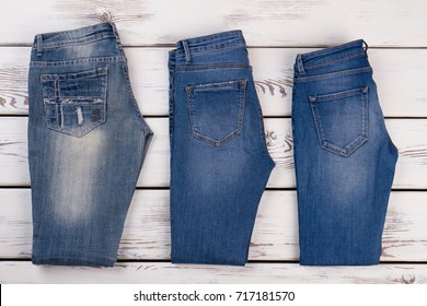 Different types of jeans on wooden showcase. Choose between straight, high waist or skinny pants.