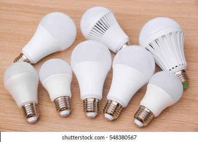 Different types of LED light bulbs on wooden background